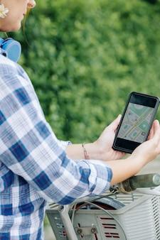 Femme touriste à vélo à l'aide de la carte gps