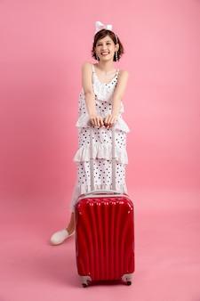 Femme touriste voyageur en vêtements décontractés avec valise de voyage isolé sur rose