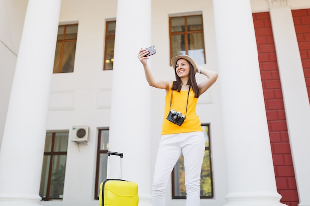 Femme touriste voyageuse prenant une photo de selfie parlant sur un téléphone portable, appelant un ami, réservant un taxi, un hôtel sur un téléphone portable en plein air. fille voyageant à l'étranger en week-end. mode de vie de voyage touristique.
