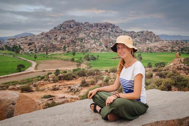 Femme touristique appréciant le paysage de rizière et de belles collines autour de l'ancienne ville de hampi en inde
