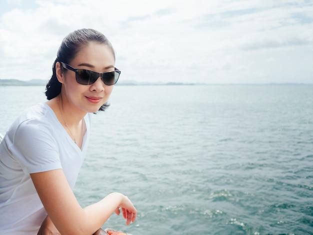 Femme touristique asiatique sur le ferry est sur le chemin de la mer