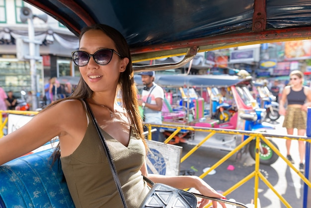 Femme touristique à la découverte de la ville de bangkok avec taxi tuk tuk