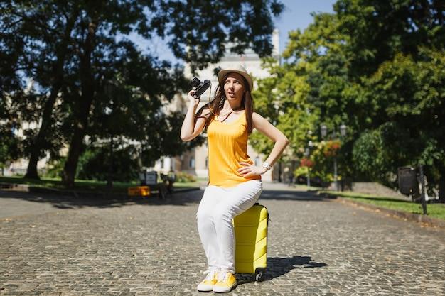 Femme touristique drôle de voyageur curieux dans des vêtements décontractés, chapeau assis sur une valise tenant un appareil photo vintage rétro dans la ville en plein air. fille voyageant à l'étranger en week-end. mode de vie de voyage touristique.