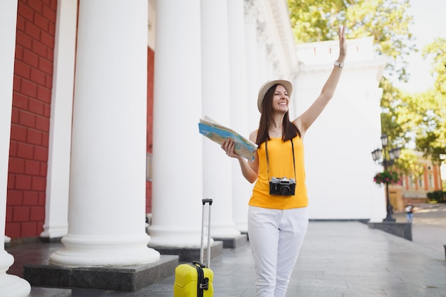 Femme touristique joyeuse avec valise, plan de la ville, appareil photo vintage rétro agitant la main pour saluer, rencontrer un ami en plein air. fille voyageant à l'étranger en week-end. mode de vie de voyage touristique.