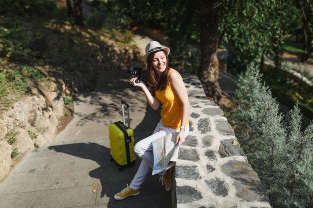 Femme touristique joyeuse en vêtements décontractés, chapeau avec valise, plan de la ville tenant un appareil photo vintage rétro dans la ville en plein air. fille voyageant à l'étranger en week-end. mode de vie de voyage touristique.
