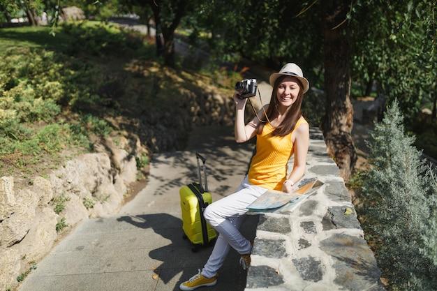 Femme touristique joyeuse voyageur au chapeau avec carte de la ville valise prendre des photos sur un appareil photo vintage rétro en plein air de la ville. fille voyageant à l'étranger pour voyager le week-end. mode de vie de voyage touristique.