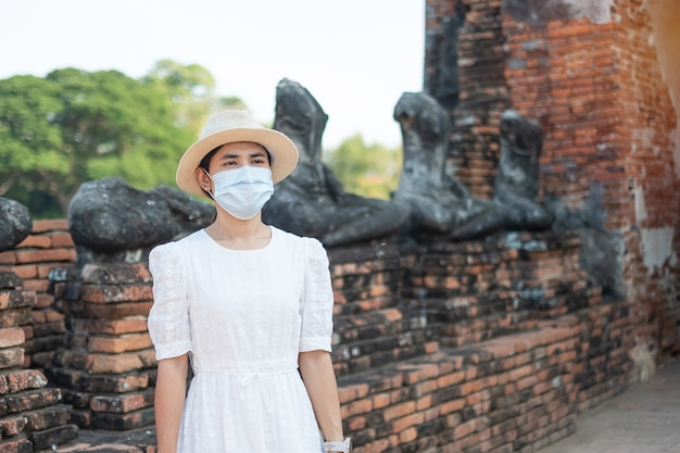 Femme touristique portant un masque chirurgical visitant le temple wat chaiwatthanaram