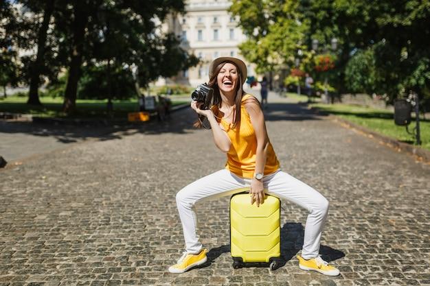 Femme touristique riante dans des vêtements décontractés, assise sur une valise avec un appareil photo vintage rétro dans la ville en plein air. fille voyageant à l'étranger pour voyager le week-end. mode de vie de voyage touristique.