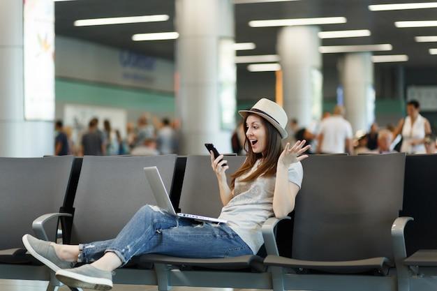 Une femme touristique surprise travaille sur un ordinateur portable, tient un appel sur un téléphone portable pour un ami réservant un taxi à l'hôtel écarte les mains dans le hall de l'aéroport