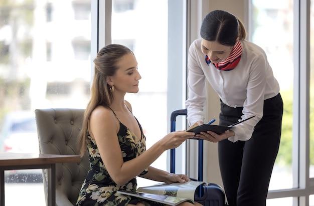 Femme touristique va remplir et signer l'enregistrement de l'hôtel dans le formulaire d'inscription au comptoir de la réception, kundenservice lors de l'arrivée à destination pour les vacances d'été