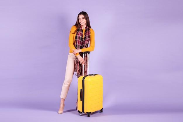 Femme touristique avec valise jaune sur l'espace de copie de fond violet