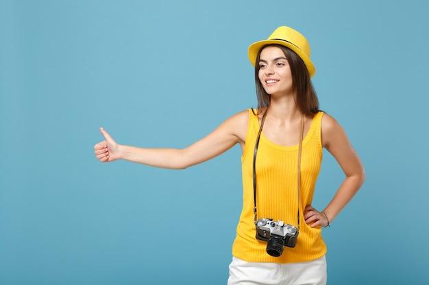 Femme touristique en vêtements décontractés d'été jaune et chapeau avec appareil photo sur bleu