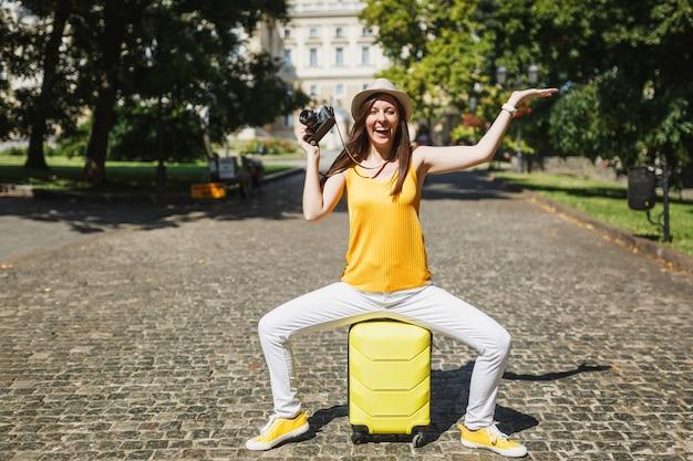 Une femme touristique de voyage ravie en vêtements décontractés s'assoit sur une valise avec un appareil photo vintage rétro écartant les mains dans la ville en plein air. fille voyageant à l'étranger le week-end. mode de vie de voyage touristique.