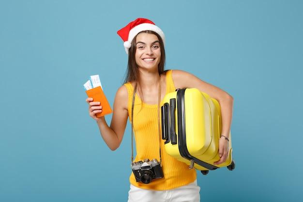 Femme touristique voyageur en bonnet de noel, vêtements décontractés jaunes tenant un sac de billets appareil photo sur bleu