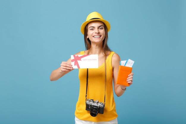 Femme touristique voyageur en chapeau jaune de vêtements décontractés tenant un appareil photo de carte-cadeau de billets sur bleu