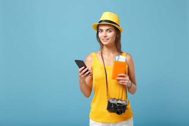 Femme touristique voyageur en chapeau jaune de vêtements décontractés tenant un appareil photo de téléphone portable sur bleu