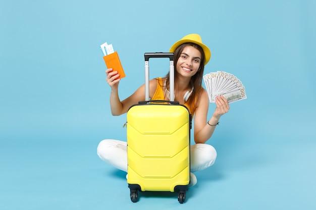 Femme touristique voyageur en chapeau de vêtements décontractés d'été jaune tenant des billets de bagages sur bleu