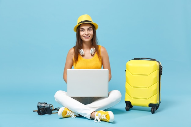 Femme touristique voyageur en vêtements décontractés jaunes, chapeau avec appareil photo pour ordinateur portable valise ordinateur portable sur bleu