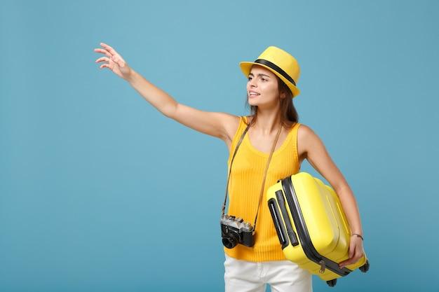 Femme touristique voyageur en vêtements décontractés jaunes, chapeau avec appareil photo valise sur bleu