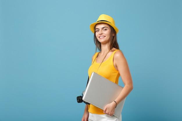 Femme touristique voyageur en vêtements d'été jaunes, chapeau avec ordinateur portable sur bleu