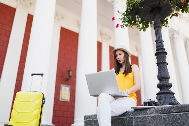 Femme touristique voyageuse concernée dans des vêtements décontractés, chapeau avec valise assis à l'aide de travail sur ordinateur portable en plein air de la ville. fille voyageant à l'étranger le week-end. mode de vie de voyage touristique.