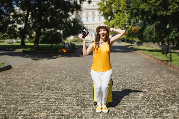Femme touristique voyageuse excitée au chapeau assis sur une valise tenant un appareil photo vintage rétro accroché à la tête en plein air. fille voyageant à l'étranger pour voyager le week-end. mode de vie de voyage touristique.