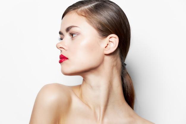 La femme tourna la tête vers les lèvres rouges, les épaules nues, la peau claire