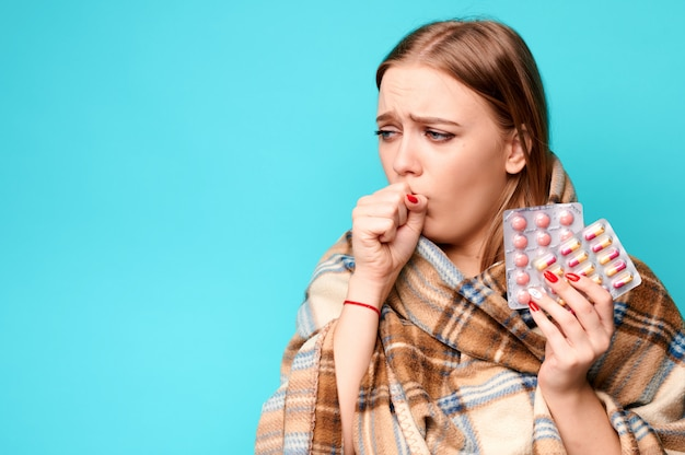 Femme tousse et tient des pilules dans ses mains enveloppées dans un plaid.