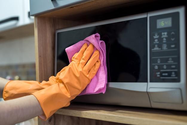 Femme tout en nettoyant la surface d'un bureau de cuisine avec une éponge dans ses gants en caoutchouc. travaux ménagers