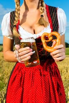 Femme avec tracht, bière et bretzel en bavière