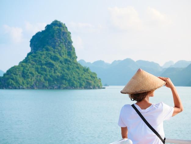Femme avec traditionnel en regardant unique vue sur la baie d'halong, vietnam.