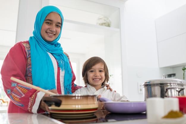 Femme traditionnelle musulmane avec petit fils dans la cuisine blanche moderne