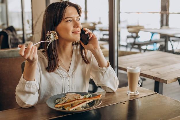 Femme en train de déjeuner dans un café, manger de la salade