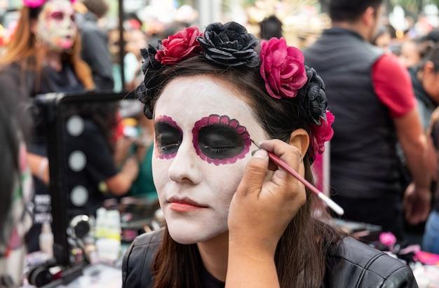 Femme en train d'être convertie en catrina avec un diadème rose dans le jour traditionnel des morts à mexico
