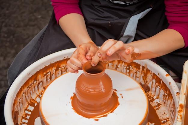Femme en train de faire de la poterie d'argile