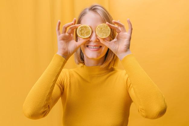 Femme avec des tranches de citron devant les yeux dans une scène jaune