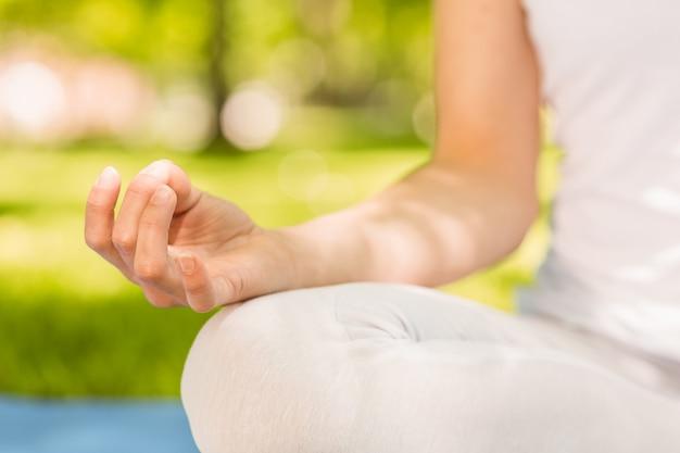 Femme tranquille, faire du yoga dans le parc par une journée ensoleillée
