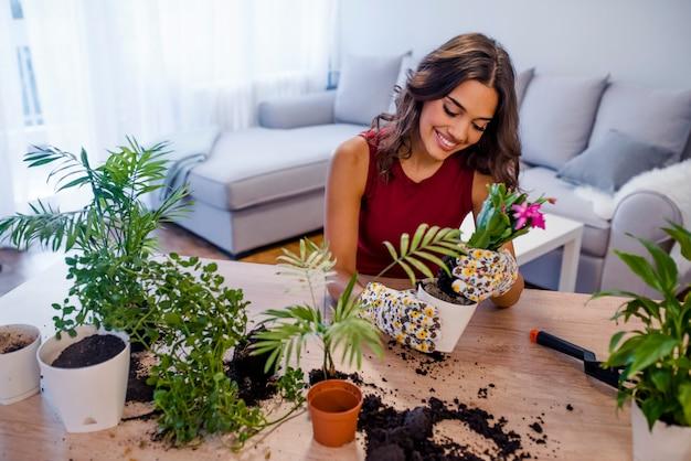 Femme transplantant une plante dans un nouveau pot.