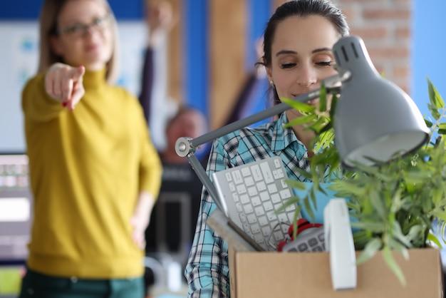 Femme transportant une boîte d'effets personnels au bureau