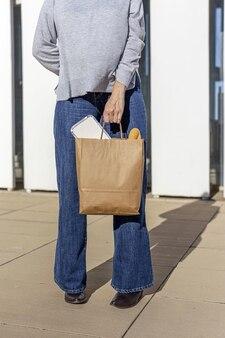 Femme transportant du papier recyclable sac de nourriture à emporter