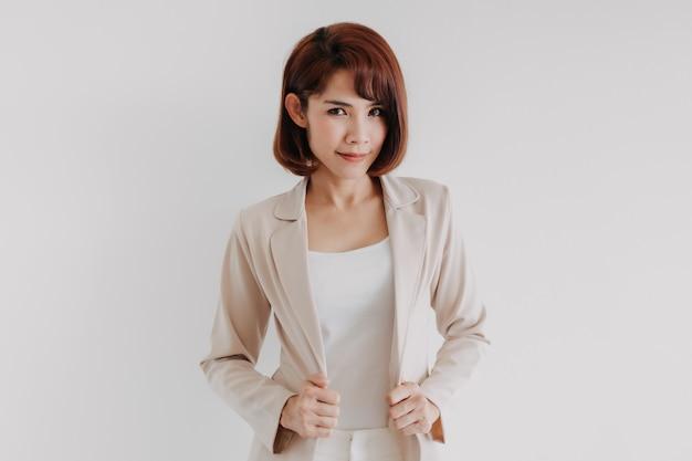 Femme de travail asiatique confiante en blazer beige isolé sur blanc