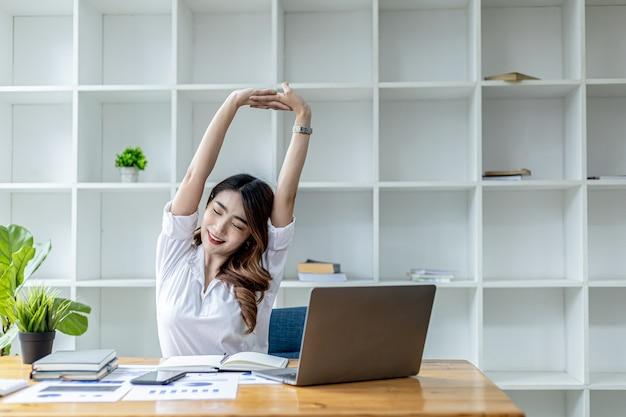 Femme de travail asiatique relaxante, femme d'affaires au bureau, elle se détend après avoir travaillé dur pendant longtemps, provoquant fatigue et stress pour faire une pause, elle a le syndrome du bureau. concept de travail acharné.