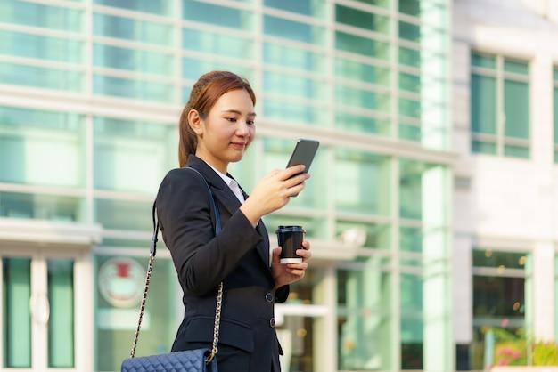 Femme de travail exécutive asiatique tenant une tasse de café et à l'aide d'un téléphone mobile dans la rue avec des immeubles de bureaux en arrière-plan à bangkok, thaïlande.