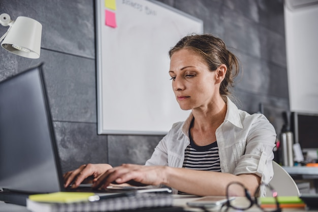 Femme travaillant à l'aide d'un ordinateur portable au bureau