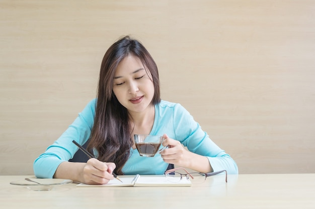 Femme travaillant assis pour boire un café dans une tasse