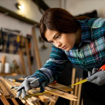 Femme travaillant en atelier mesurant des planches de bois