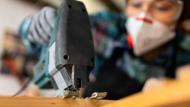 Femme travaillant en atelier avec perceuse à percussion close up