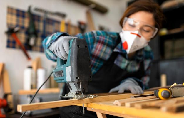 Femme travaillant en atelier avec perceuse à percussion
