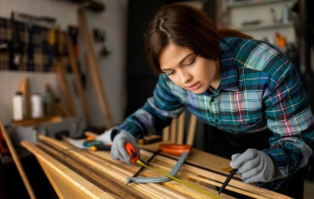 Femme travaillant en atelier avec ruban à mesurer