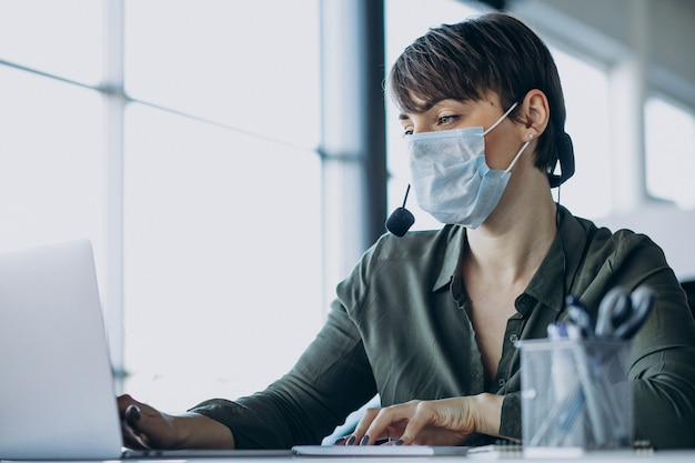 Femme travaillant au studio d'enregistrement et portant un masque